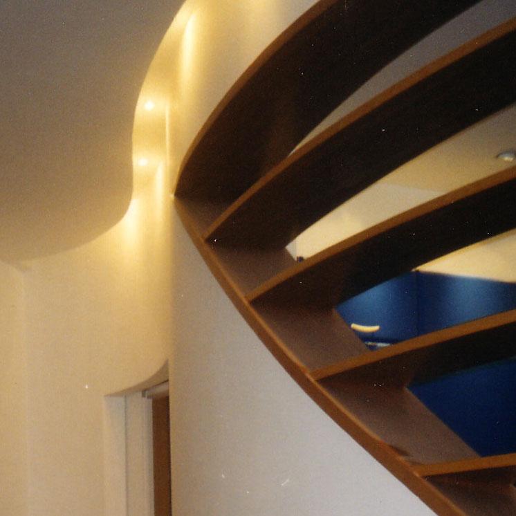 Parete curva con luce diffusa e libreria a giorno. Pavimento in parquet.